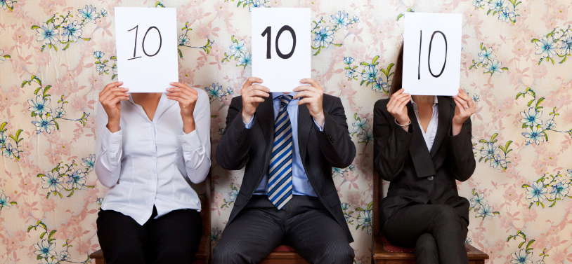 A man and two women dressed in business attire cover their faces with sheets of paper indicating perfect 10 scores.